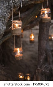 Beautiful decorated romantic place for a date with jars full of candles hanging on tree and standing on a sand