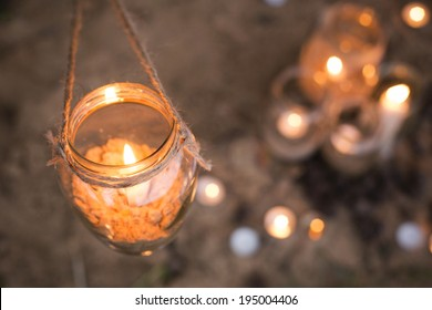 Beautiful decorated romantic place for a date with jars full of candles hanging on tree and standing on a sand. Copy Space