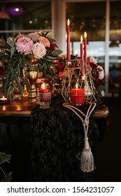 Beautiful, decorated table with flower decorations and red candles. Christmas evening or wedding party decoration.