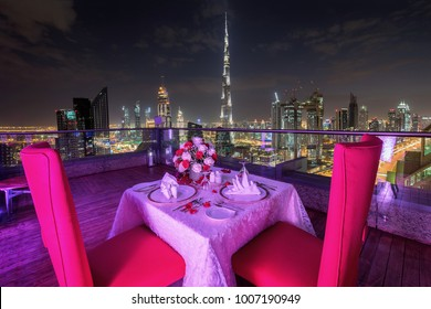 Beautiful decorated table for two persons in front of Dubai skyline