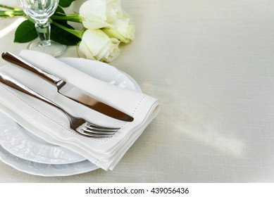 Beautiful decorated table with white plates, crystal glass, linen napkin, cutlery and white rose flower on tablecloths, with space for text