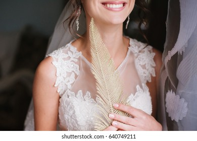 beautiful decoration. Golden feathers. Gold obrruchka. jewelry The bride in a white dress smiles