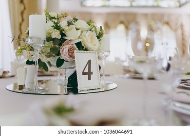 Beautiful decoration of a wedding banquet in a restaurant in pastel colors. Decoration of banquet dinner table vase with flower arrangement, candlestick, card with number of table in frame.
