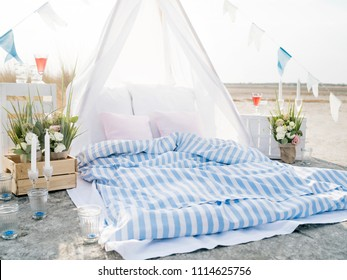 Beautiful decorations and soft mattress for romantic date lying on beach on sunny day.