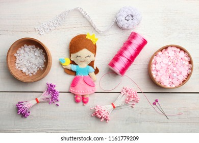 Beautiful decorative doll on wooden background. Concept handmade. Top view.