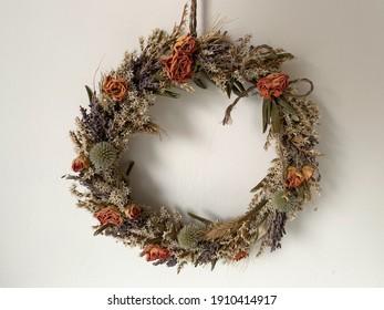 Schöner dekorativer Kranz getrockneter Pflanzen und Blumen auf einer weißen Wand einzeln Nahaufnahme