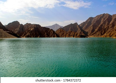 Beautiful deep green Hatta lake with rocky Hajar Mountains on background. Overview of Hatta dam in UAE. Picturesque nature in Middle East.