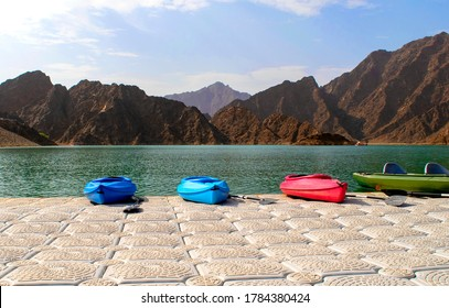 Beautiful deep green Hatta lake between Hajar Mountains with many colorful kayaks parked on a pier. Overview of Hatta dam in UAE. Canoe without people.