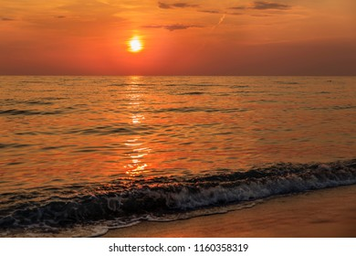 Beautiful deep red sunset on the beach and sea