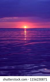 Beautiful deep violet sunset with orange sunlight on horizon line and calm sea waves