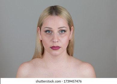 Beautiful defenseless blonde  woman  with bare shoulders on an isolated gray background. Women's Insecurity Concept