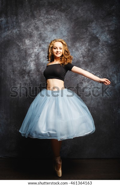 beautiful and delicate ballerina in a studio on gray background
