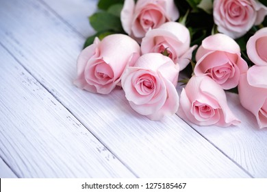 Beautiful and delicate bouquet of blooming roses in soft pink color on cream-colored wood background. Selective focus. Love, Romance, Valentine's Day, Anniversary, Mother's Day. Card and invitation