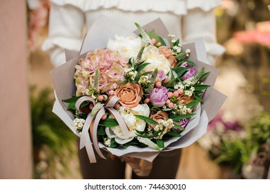 Beautiful and delicate bouquet of tender flowers in the female hands on the light background