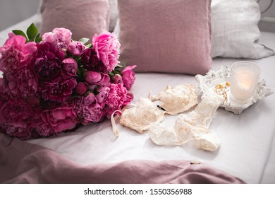 Beautiful delicate silk lingerie is lying on linen bedclothes with peonies bouquet and candles. Womans fashion accessories, underwear, flowers, jewelry on grey background. Romantic morning.