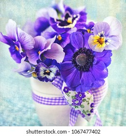 Beautiful delicate violet flowers close-up in a vase decorated with a heart. Purple flowers.
