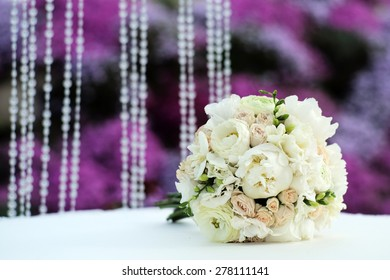 Beautiful delicate wedding bouquet of roses and peony in pastel colours lying on table in broad daylight outdoor on purple and violet holiday background copyspace, horizontal picture