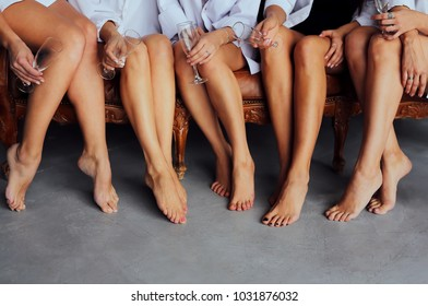 Beautiful delicate women's feet. A diverse group of girlfriends enjoying at a fun party with glasses. The slender legs of the models for a pedicure