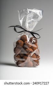 Beautiful and delicious chocolate truffles bag with elegant black ribbon isolated on grey background. Shooting in studio.