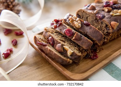 Beautiful delicious homemade Christmas dried fruit cake on wooden table with decorating items for celebrating festive season