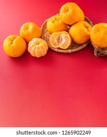 Beautiful and delicous tangerine isolated on red background with bamboo sieve, new modern auspicious and jubilant concept of chinese new year, close up, copy space