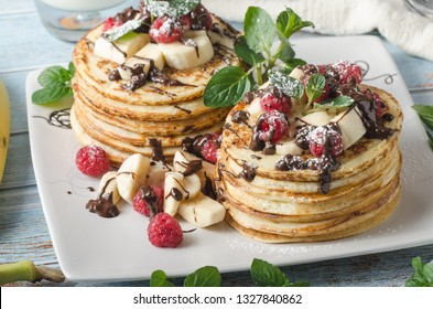 Beautiful and delish dessert, fresh pancakes with dark chocolate and fresh fruit with mint