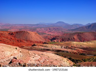 Beautiful desert view, barren multicolored hills in red, pink, purple and yellow colors, few green fields, distant mountains and blue sky in Southern Morocco, North West Africa.