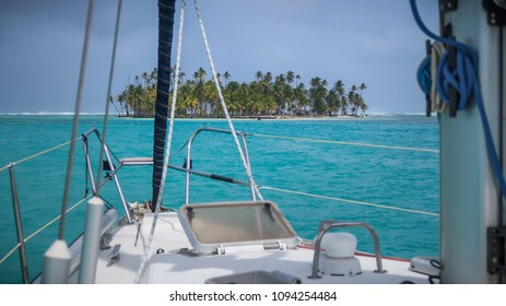 A beautiful deserted island with green palm trees seen from a white sailing yacht surrounded by turquoise water in the San Blas Islands, Panama.