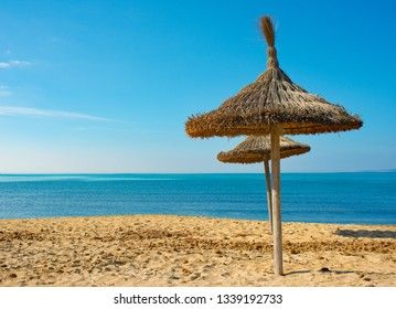 Beautiful deserted Spanish beach with straw sunshades against a clear blue sky looking down on the Mediterranean Sea.