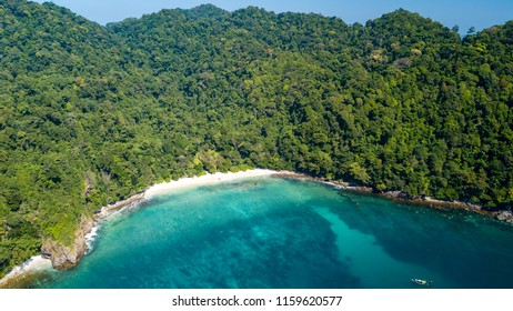 A beautiful, deserted tropical beach surrounded by lush green jungle and tropical coral reef (Mergui Archipelago, Myanmar)