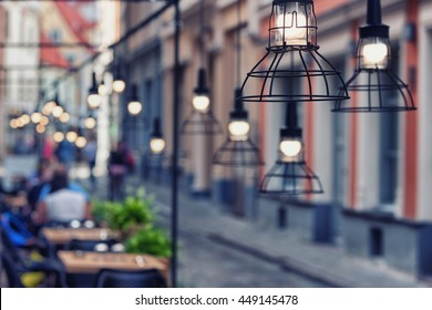 Beautiful design lamps over the tables of the restaurant on a stone street in the evening the old town of Riga. Blurry