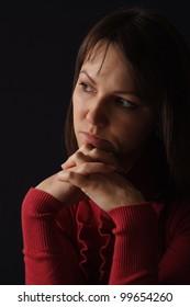 Beautiful desperate caucasian girl in red sitting on a dark background