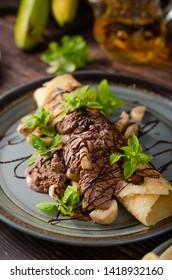 Beautiful dessert with homemade chocolate ice cream, basil leaves and banana, topped with dark chocolate