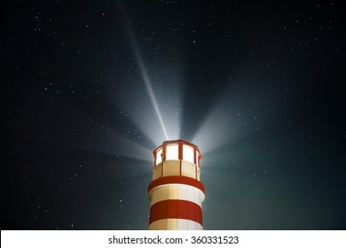 Beautiful detail of white and red lighthouse with shining light and stars