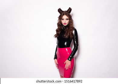 Beautiful devil brunette model vamp mistress dominatrix bdsm woman in glamour fetish latex dress with hair horns posing on white background