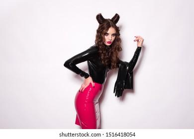 Beautiful devil brunette model vamp mistress dominatrix bdsm woman in glamour fetish latex dress with hair horns posing on white background