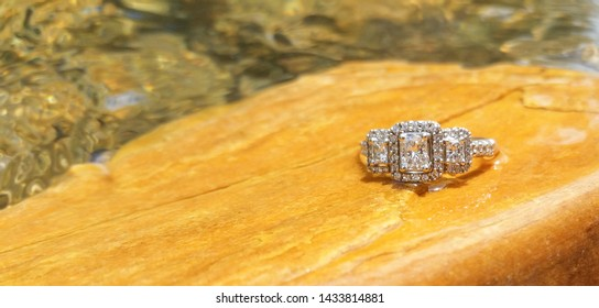 A  beautiful diamond engagement ring  rests on  stones rocks in a  gentle  stream of a  river bed, babbling brook, stream.  The flat  yellow gold  rock sets off the  silver and diamonds in the ring.