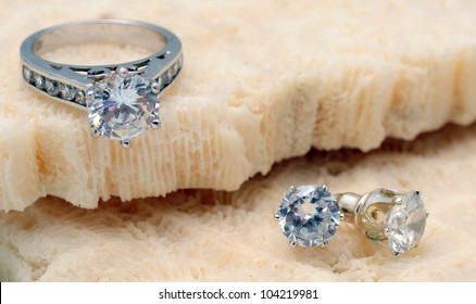 Beautiful diamond engagement ring and diamond stud earrings on coral
