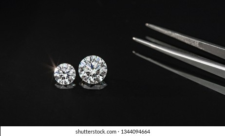 Beautiful diamonds compare with tweezers on black reflection background