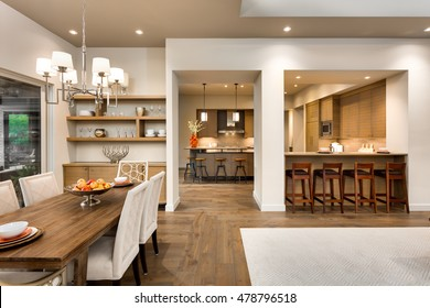 Beautiful Dining Room and Kitchen Interior in New Luxury Home. Features hardwood flooring, exquisite kitchen and bar seating, table with decor