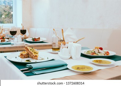 Beautiful dining setup with wine and water glasses, cutlery in green napkins, food served on white plates, arranged by catering service in a modern light restaurant, cafe. Italian European cuisine