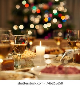 Beautiful dining table full of a variety of delicious festive food and wine with a Christmas tree in the background in warm mood