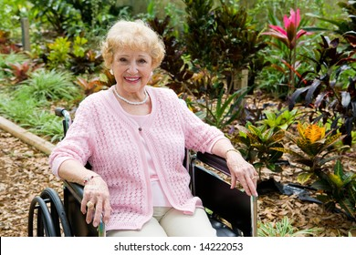 Beautiful disabled senior woman in the garden.   Horizontal view with room for text.