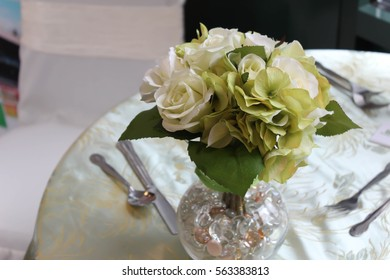 beautiful display of cloth flowers on a table set for dinner