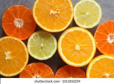 Beautiful Display of  freshly picked citrus fruits cut in half : orange, clementine and lemon on a grey background - isolated