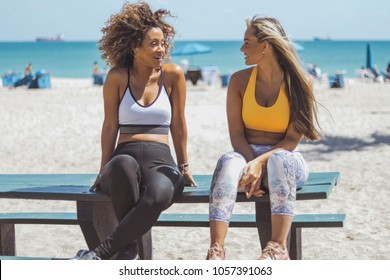 Beautiful diverse girlfriends in sportswear sitting on wooden bench on tropical coastline and enjoying time together chatting.