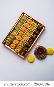 Beautiful Diwali Diya, Sweets OR Mithai arranged over moody background. Selective focus