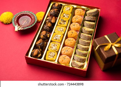 Beautiful Diwali Diya, Sweets OR Mithai and Gift boxes arranged over decorative background. Selective focus