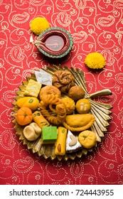 Beautiful Diwali Diya, Sweets OR Mithai arranged over moody background. Selective focus