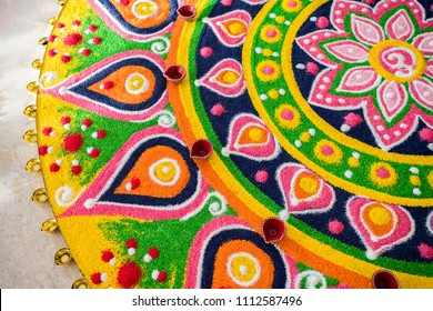 Beautiful Diwali Greeting using Diya or clay oil lamp lit and arranged over Rangoli made by multi coloured rice grains
